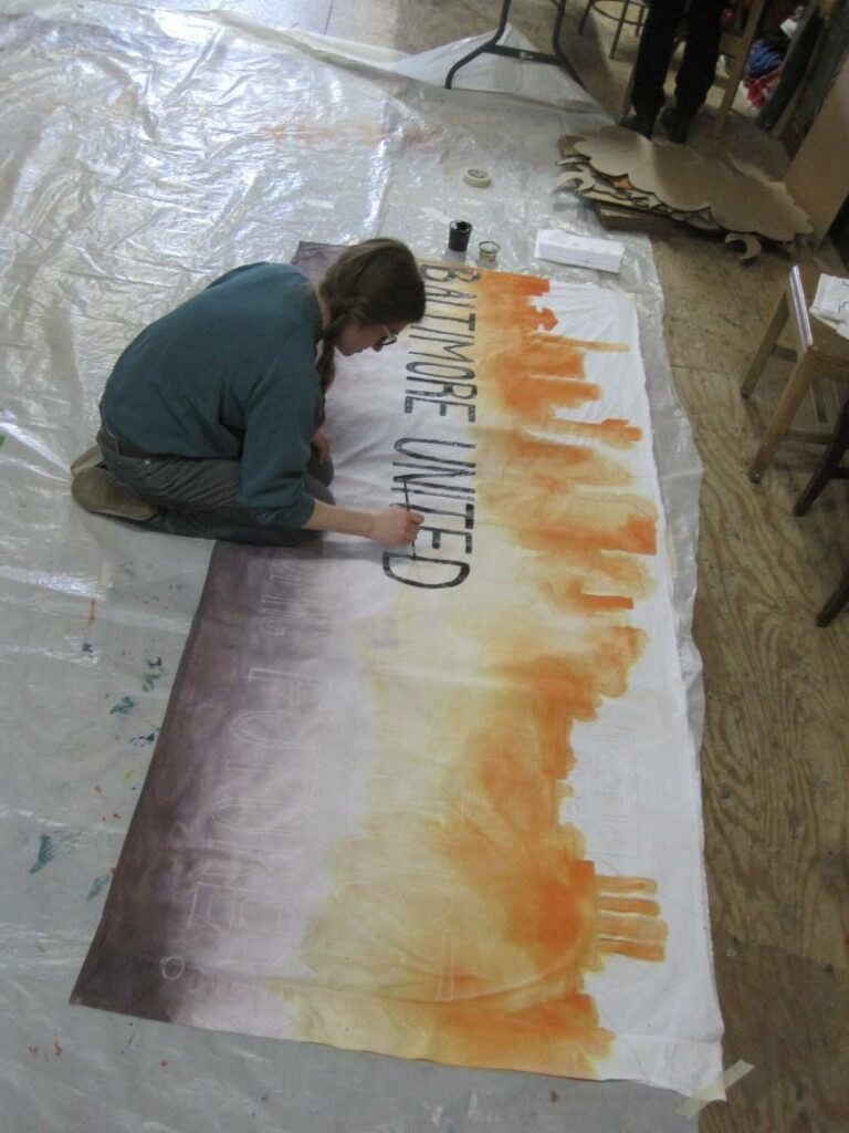 """Taylor Smith-Hams, CCAN's Baltimore organizer and art cluster co-leader, painting a banner for the Baltimore contingent, which reads, """"Baltimore United for A Just, Clean Energy & Economic Future."""" Photo by Valeska Populoh."""