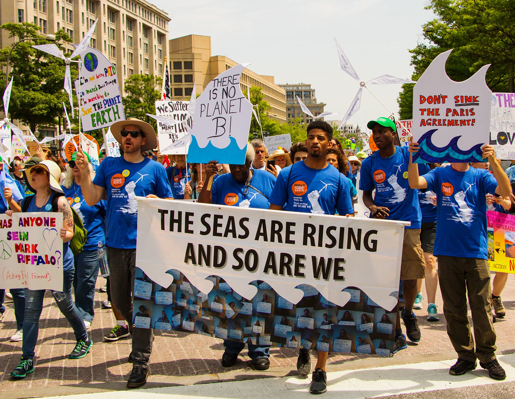 resist with us - activists carrying banners to protest climate change