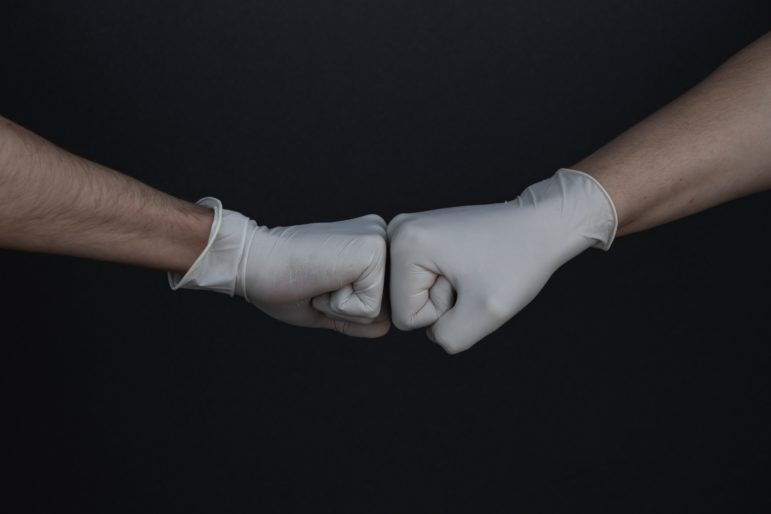 fist bump against dark background. Both fists have surgical latex gloves on.