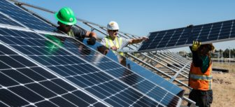 construction workers with hard hats position solar panels on metal frames outdoors